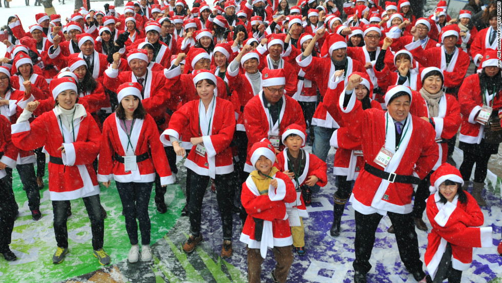 "People in Santa Claus outfits imitate South Korean rapper Psy's famous ""Gangnam Style"" dance outside offices in Seoul, South Korea, on Wednesday, December 5. The dance marked the start of a charity mission to hand out gifts to children."
