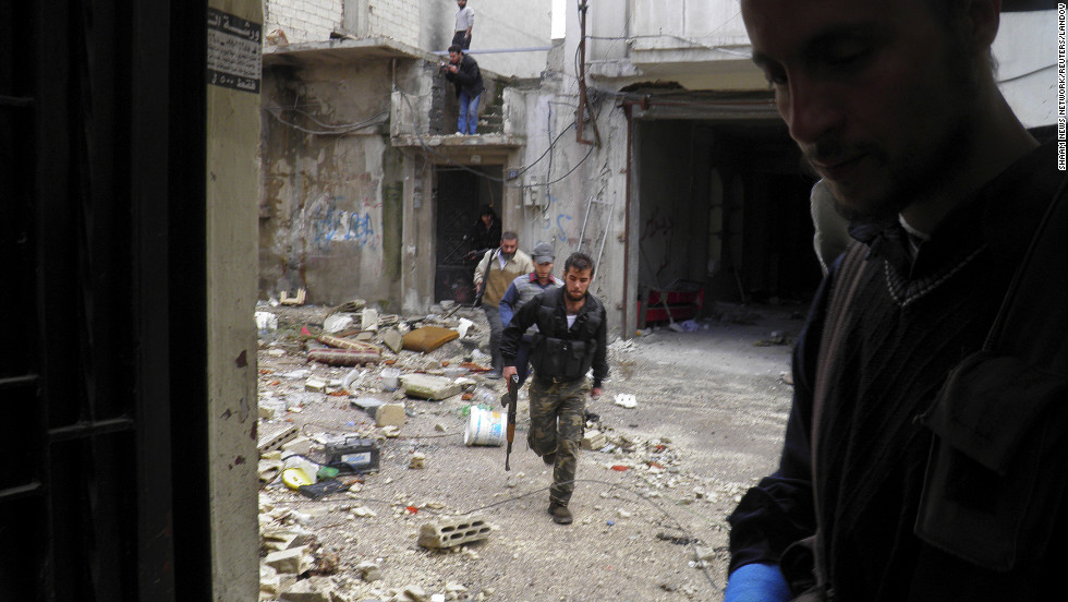 In this handout from the Shaam News Network, Free Syrian Army fighters take cover in destroyed buildings during clashes with regime forces on December 4.