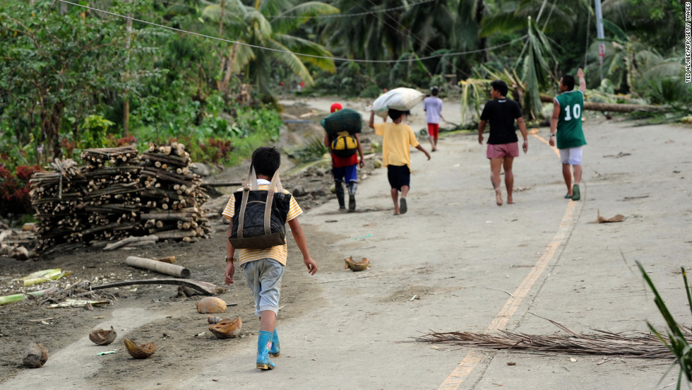 Residents walk down a road covered in debris after the storm in New Bataan on December 5.