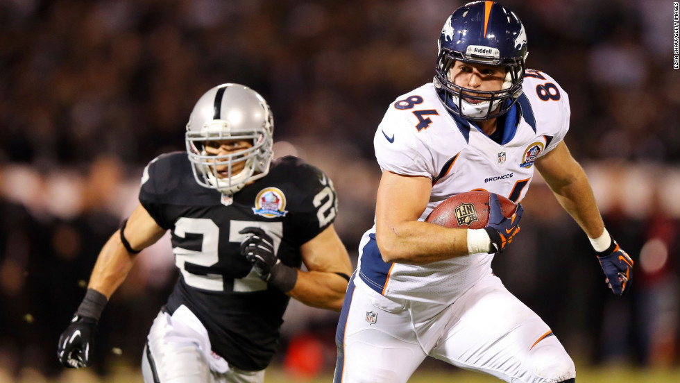 Jacob Tamme of the Denver Broncos runs the ball as Matt Giordano of the Oakland Raiders pursues him on Thursday.