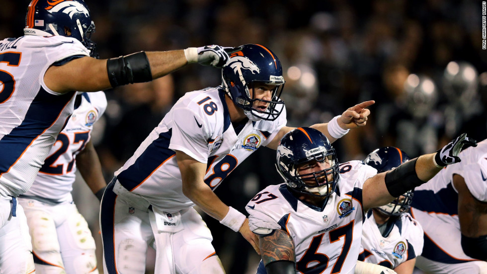 Quarterback Peyton Manning of the Denver Broncos calls out a play change behind center Dan Koppen during their game against the Oakland Raiders at Oakland-Alameda County Coliseum on Thursday, December 6, in Oakland, California.