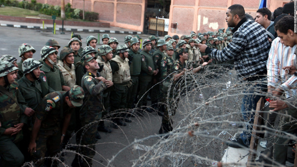 A protester tries to climb over a barbed-wire fence as Egyptian soldiers stand guard during a demonstration near the presidential palace in Cairo on Friday, December 7.