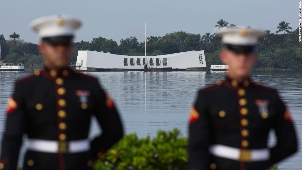A U.S. Marine firing detail stands at attention with the Arizona Memorial in the background in Pearl Harbor, Hawaii.