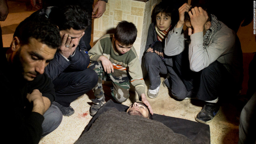 Syrians mourn a fallen fighter at a rebel base in the al-Fardos area of Aleppo on Saturday, December 8.