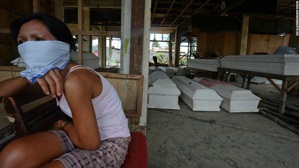 A resident sits next to coffins at the old market in New Bataan on December 8.
