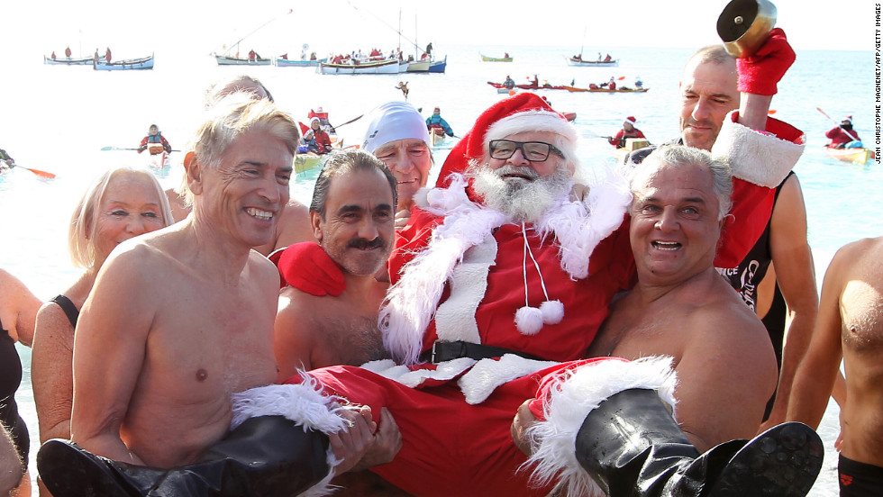 Beachgoers carry a man wearing a Santa Claus costume on the Mediterranean coast on Saturday, December 8, in Nice, France.