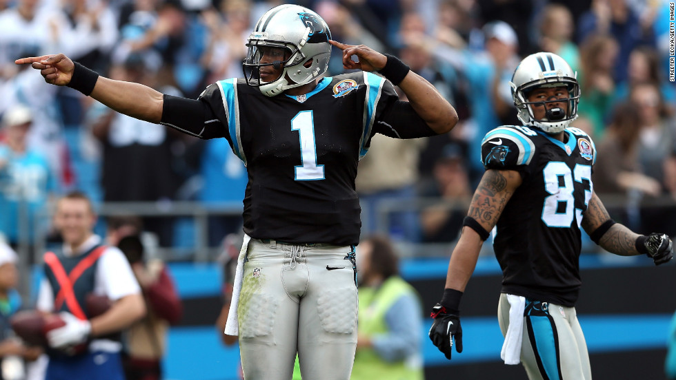 Cam Newton of the Panthers signals a first down as teammate Louis Murphy watches on Sunday.