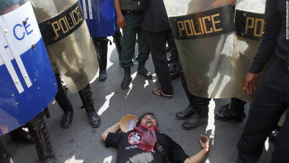 A Boeung Kak Lake resident lies on the road as she protests next to riot police during a march to celebrate Human Rights Day in Phnom Penh, Cambodia, on December 10.