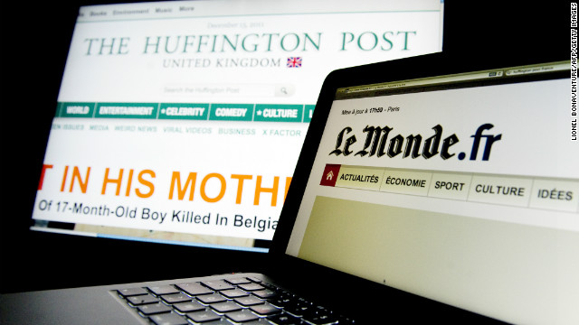 (File photo) Computer screens feature pages of the Huffington Post and Le Monde newspaper websites.