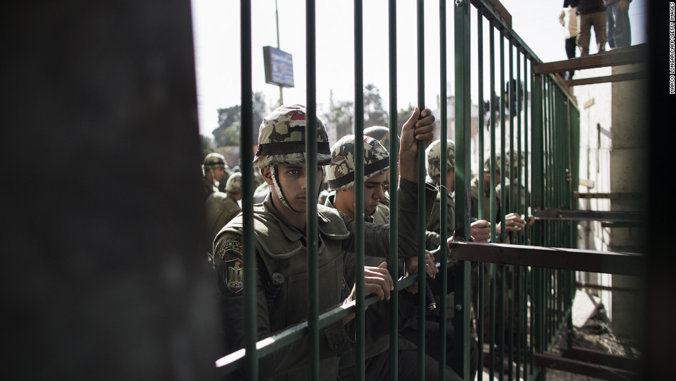 Egyptian army troops stand guard in front of a metal barricade on December 11.