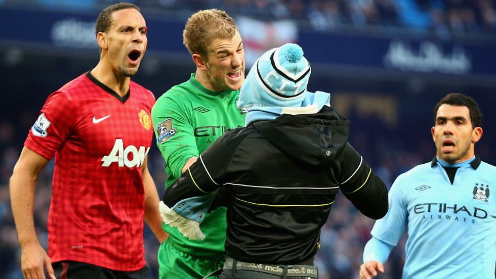 Manchester City goalkeeper Joe Hart confronts a pitch invader trying to harass Manchester United's Ferdinand, who had been hit in the face by a coin thrown from the crowd.