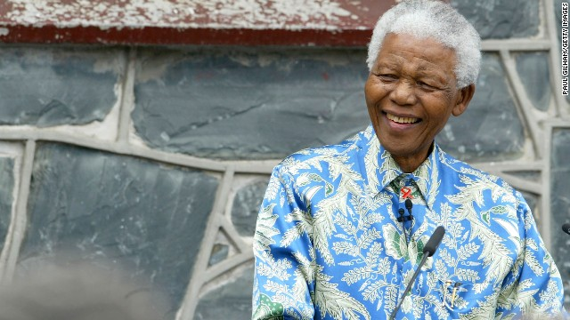 Mandela sits outside his former prison cell on Robben Island on November 28, 2003 ahead of his AIDS benefit concert at Green Point Stadium in Cape Town.