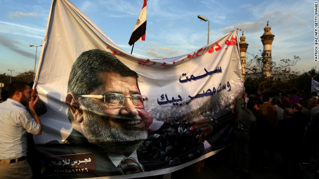 embers of Egypt's Muslim Brotherhood carry a banner with a picture of Mohamed Morsi in Cairo on December 11, 2012.
