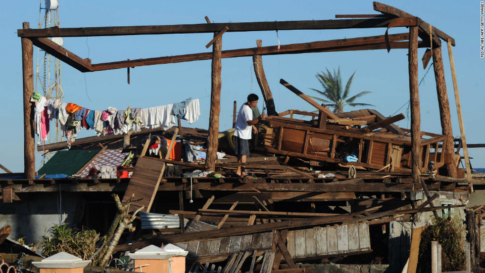 A resident stands on his destroyed house in Cateel on December 11.