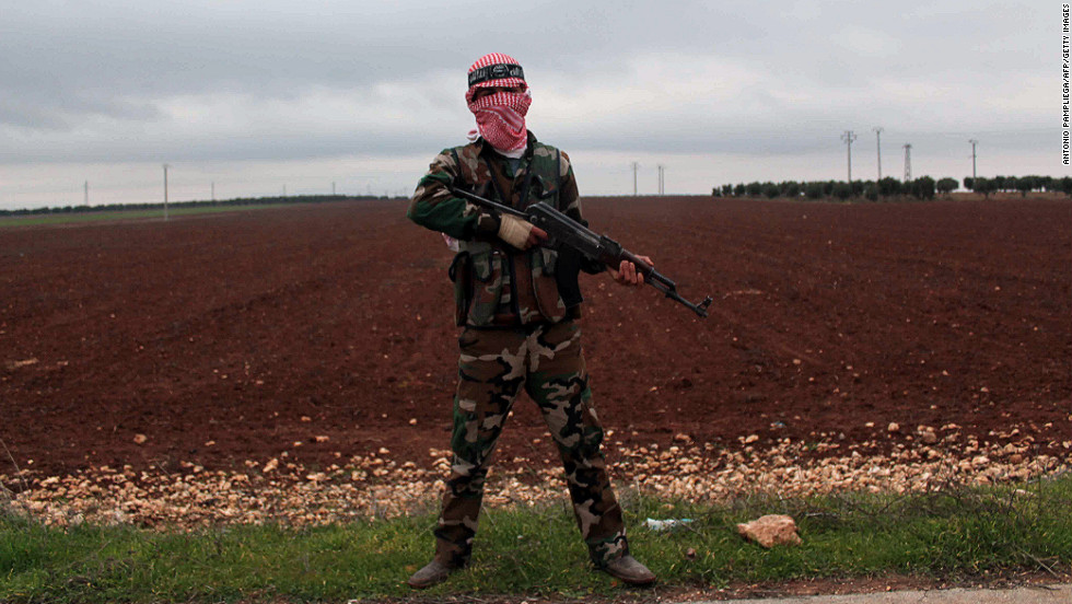 "A member of the Syrian opposition's Al-Buraq Brigade stands guard on a main road in the northern Syrian town of Ain Dakna near the Turkish border on Monday, December 10. Click through to view images of the fighting from December, or<a href=""http://www.cnn.com/2012/12/04/middleeast/gallery/syria-unrest-november/index.html"" target=""_blank""> see photos of the conflict from November</a>."