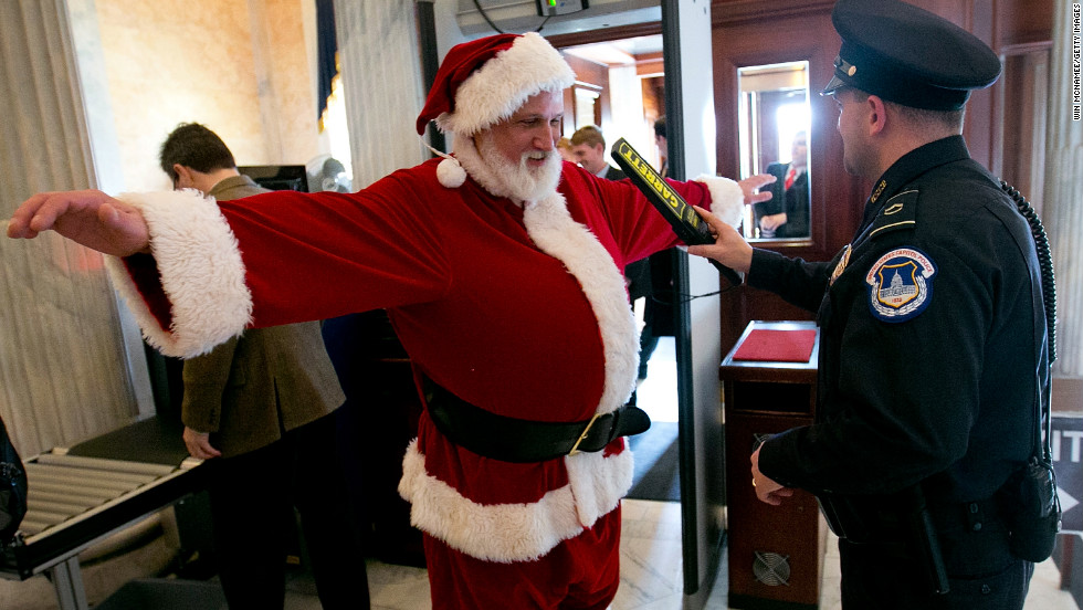 Police check a man dressed as Santa Claus as he passes through a metal detector at the U.S. Capitol on Wednesday, December 12, in Washington.