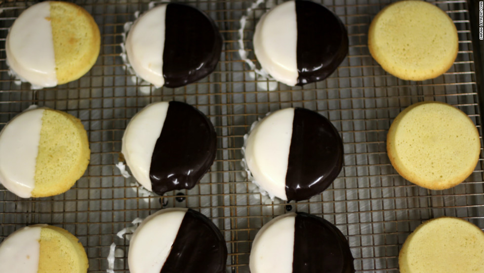 "Black-and-white cookies are a New York City staple. The black-and-white, sometimes referred to as a ""half moon,"" gets its name because it is glazed with both chocolate (black) and vanilla (white) icing."