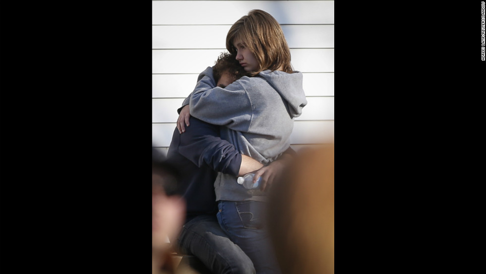 People comfort each other near Sandy Hook Elementary School on December 14.