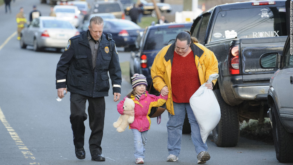 A child and her mother leave a staging area outside Sandy Hook Elementary School in Newtown, Connecticut, on December 14.
