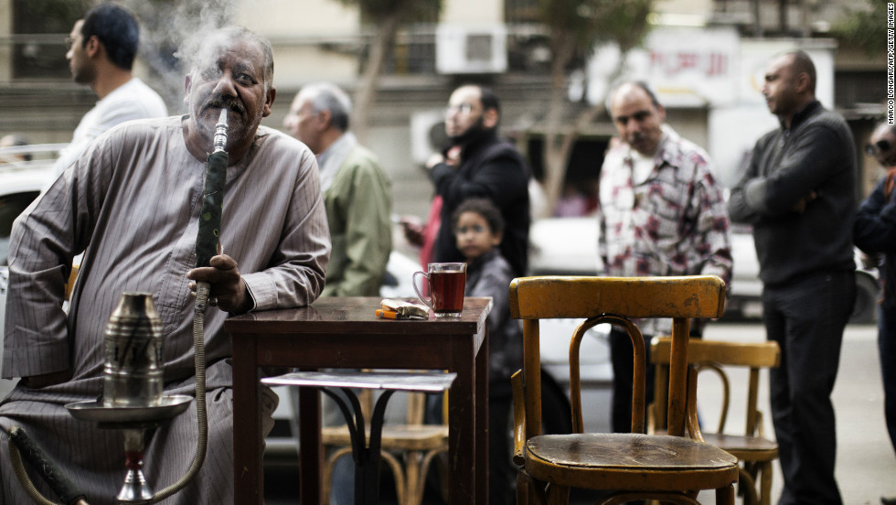 An Egyptian man smokes a waterpipe, known locally as Shisha, as others queue outside a polling station in central Cairo to cast their votes on a new constitution.