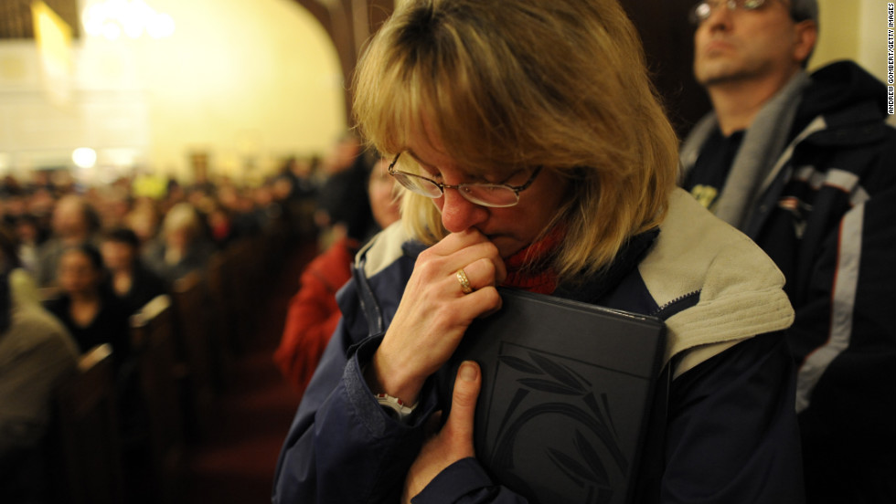 A woman bows her head during a vigil for the shooting victims at St. Rose Church.