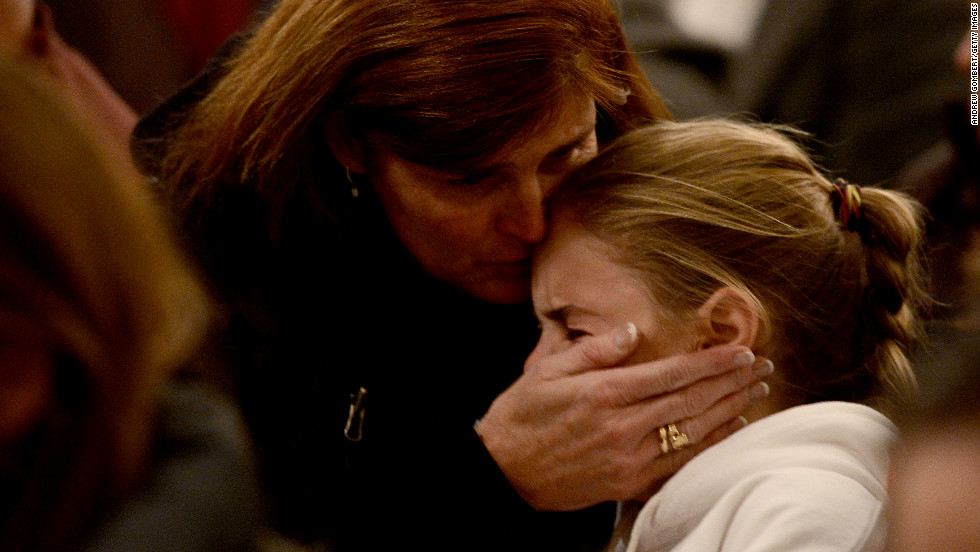 Women comfort each other during the vigil at St. Rose Church.