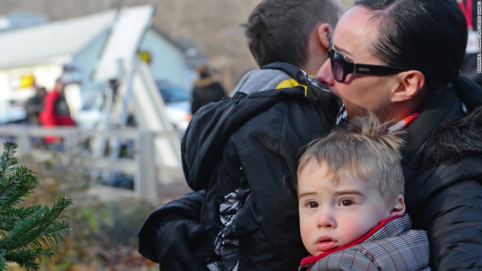 A mother hugs her children after paying tribute to the victims in Newtown on Saturday, December 15.