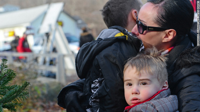 A mother hugs her children after paying tribute to the victims in Newtown, Connecticut, on Saturday.
