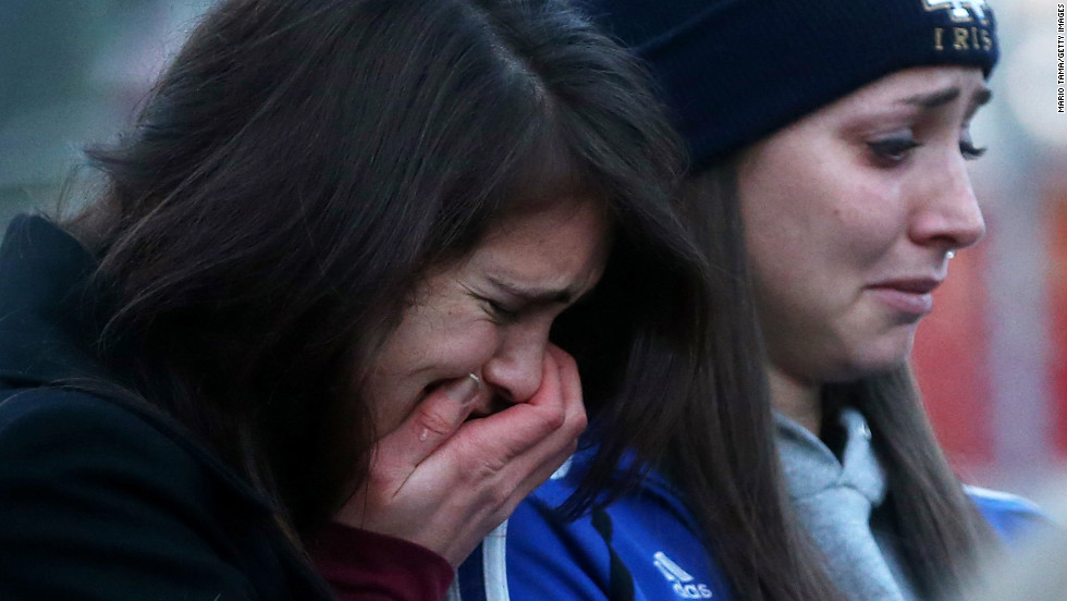People are overcome with emotion Saturday at a makeshift memorial near Sandy Hook Elementary School in Newtown.