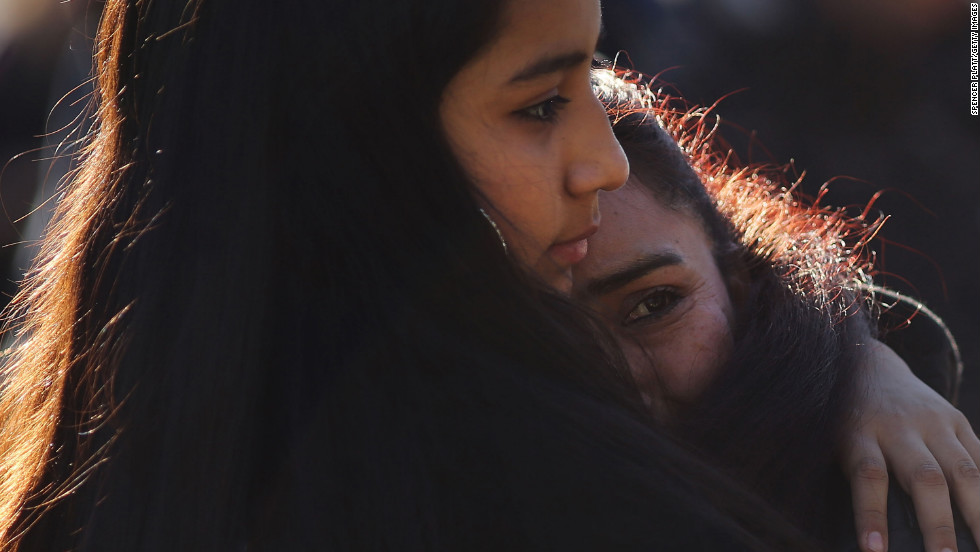 Claudia Urbiana and daughter Jocelyne Cardenas, left, hug outside of the entrance to the Sandy Hook school.