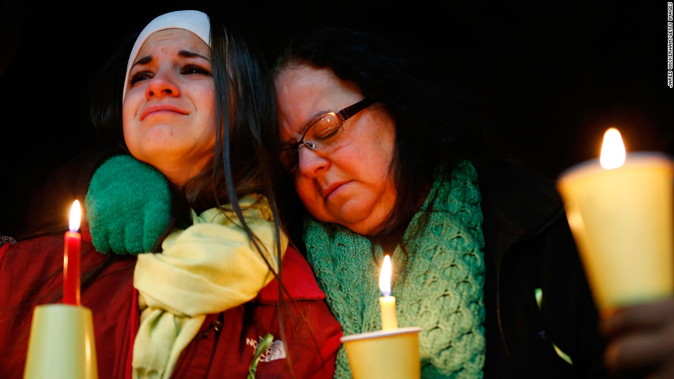 Donna Soto, right, mother of Victoria Soto, the first-grade teacher at Sandy Hook Elementary School who was shot and killed while protecting her students, hugs her daughter Karly while mourning their loss at a candlelight memorial at Stratford High School on Saturday, December 15, in Stratford, Connecticut.