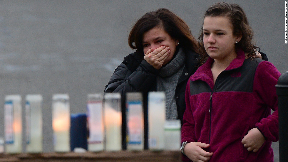 Parishioners pay their respects to the victims of the elementary school shooting while attending Mass at St. Rose of Lima Roman Catholic Church in Newtown on December 16.