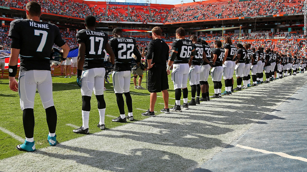 The Jacksonville Jaguars observe a moment of silence to honor the victims of the Connecticut school shooting before their game against the Miami Dolphins at Sun Life Stadium on Sunday, December 16.