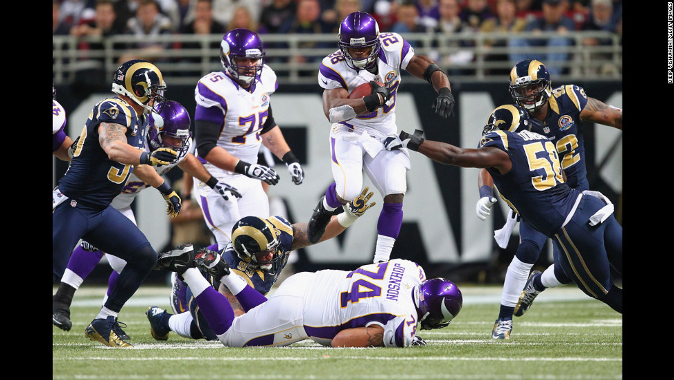 Adrian Peterson of the Vikings hurdles one of his linemen while rushing against the Rams on Sunday.