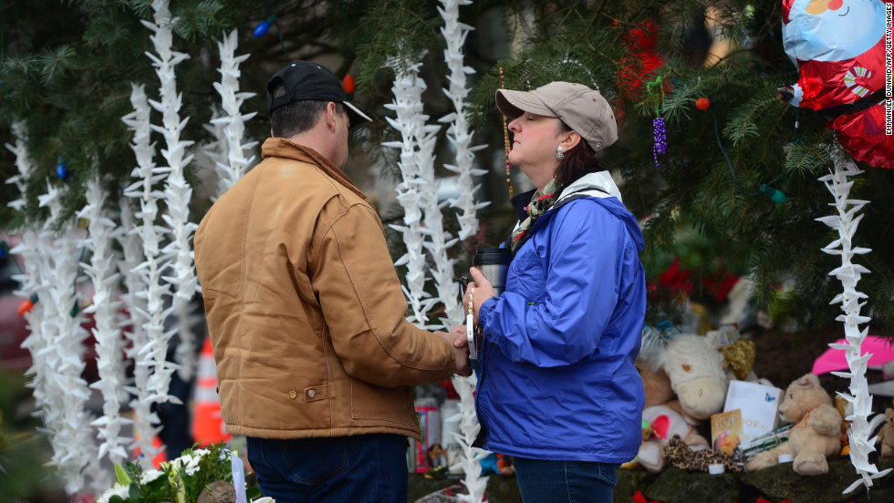 People pay their respects on December 17 at a makeshift shrine in Newtown to the victims of Friday's elementary school shooting. Funerals began Monday in the Connecticut town.