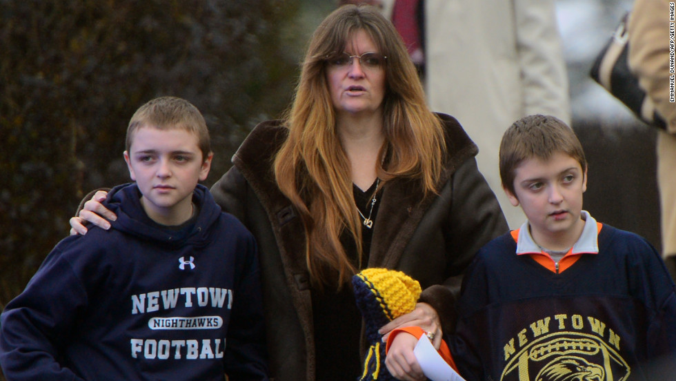 A mother and two children attend  the funeral for Jack Pinto on December 17. Children are among those crowding the funeral for the 6-year-old boy.