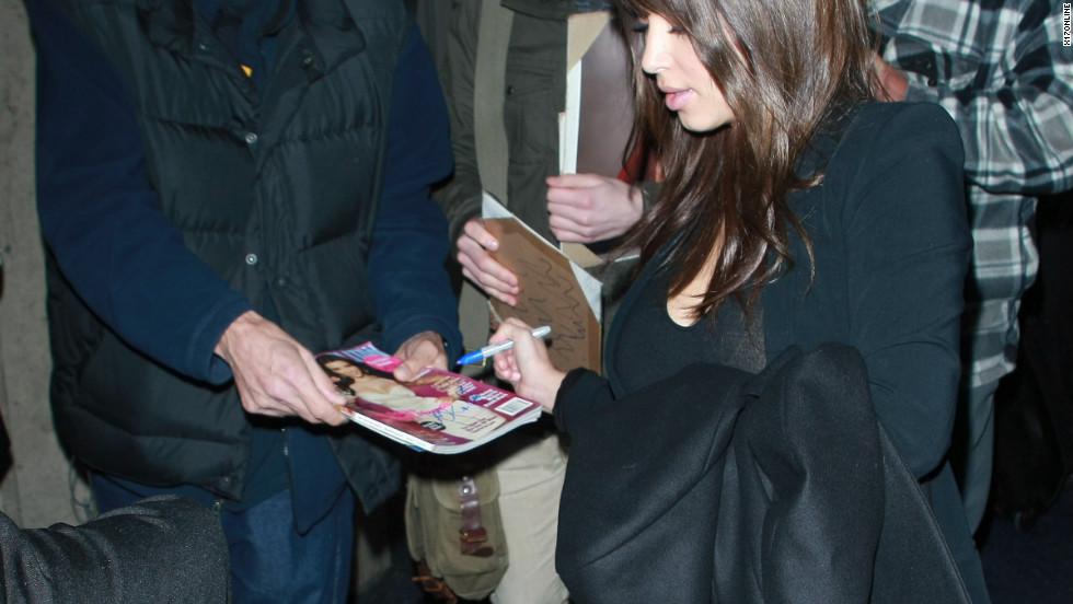 Kim Kardashian signs autographs upon arriving in Los Angeles.