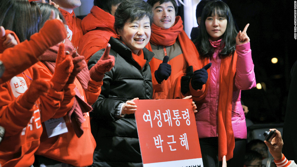 "December: South Korea's presidential candidate Park Geun-Hye holds a placard reading ""Woman President Park Geun-Hye"" during her election campaign in Seoul on December 18, the day before she won the presidency."