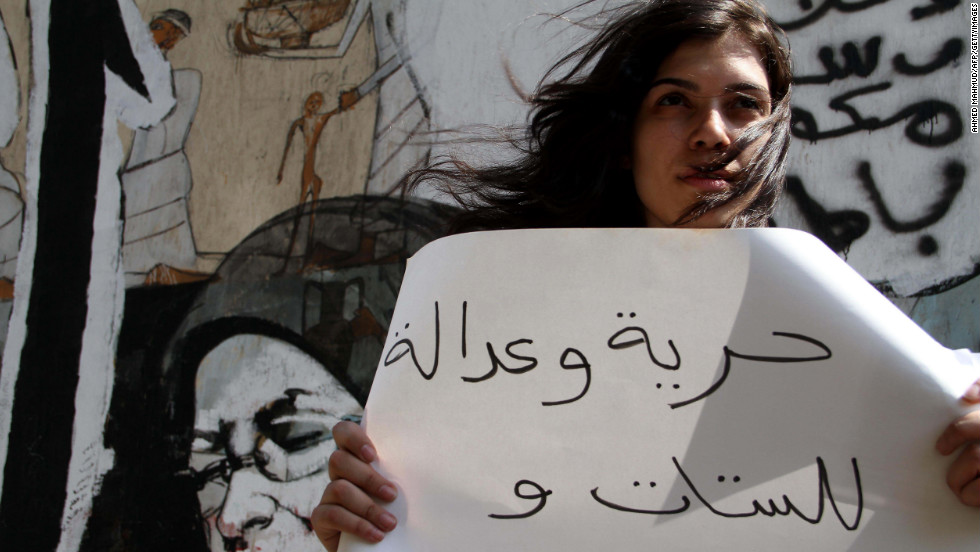 "A protester holds a sign reading ""freedom and justice for women and men"" during a demonstration against sexual harassment in Cairo, Egypt, on July 6, 2012."
