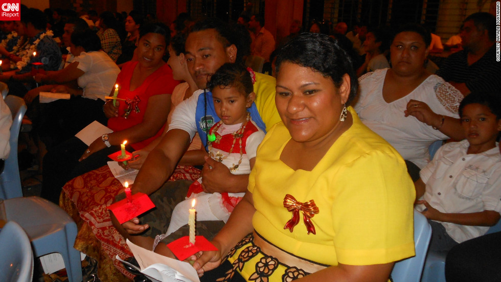 "<a href=""http://ireport.cnn.com/people/RomaniaScene"">Natalie Montanaro</a> captured this moment of a happy family attending a carol performance in the Pacific island of Tonga. ""Although we are showered with tropical sunshine, shaded by coconut palms and quenched by the cool blue of the South Pacific, it's already 'beginning to look (and feel!) a lot like Christmas,"" she said."