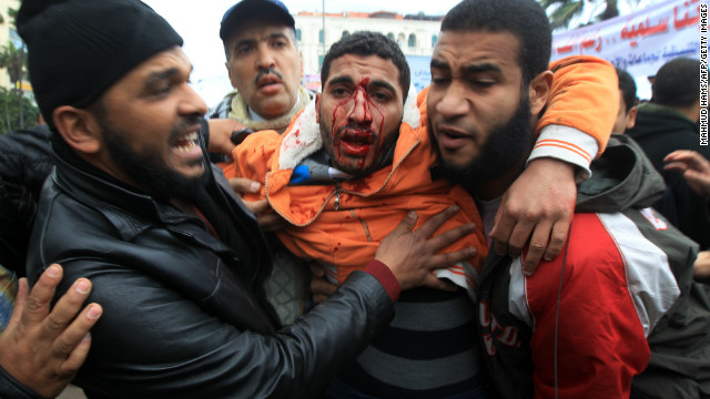 Egyptian men help a wounded comrade during clashes in Alexandria on Friday.