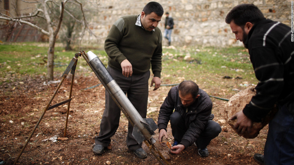 Free Syrian Army fighters prepare a homemade missile before they launch it toward the military airport in Aleppo, Syria, on Sunday, December 23.