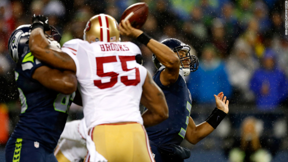 Russell Wilson of the Seattle Seahawks throws a pass under pressure from Ahmad Brooks of the San Francisco 49ers on Sunday.