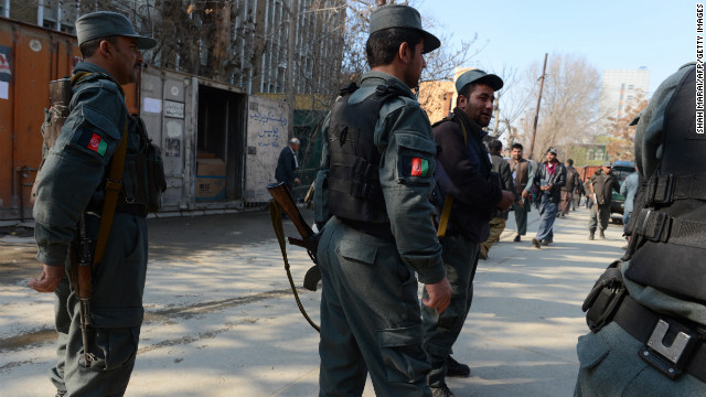 Afghan policemen stand guard at the site where a female police officer shot dead a foreign civilian adviser.