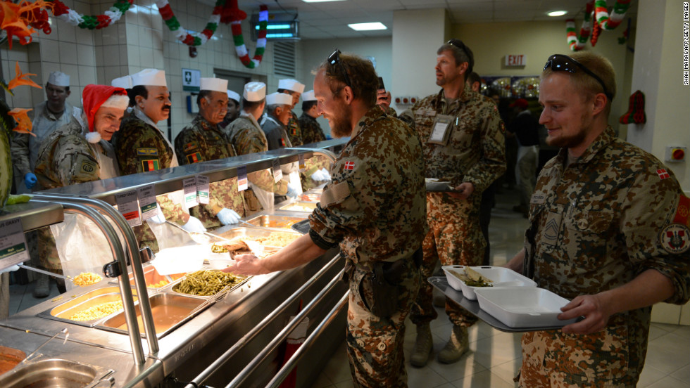 Troops with the NATO-led International Security Assistance Force collect their food during a special Christmas meal at Kabul International Airport on Tuesday.