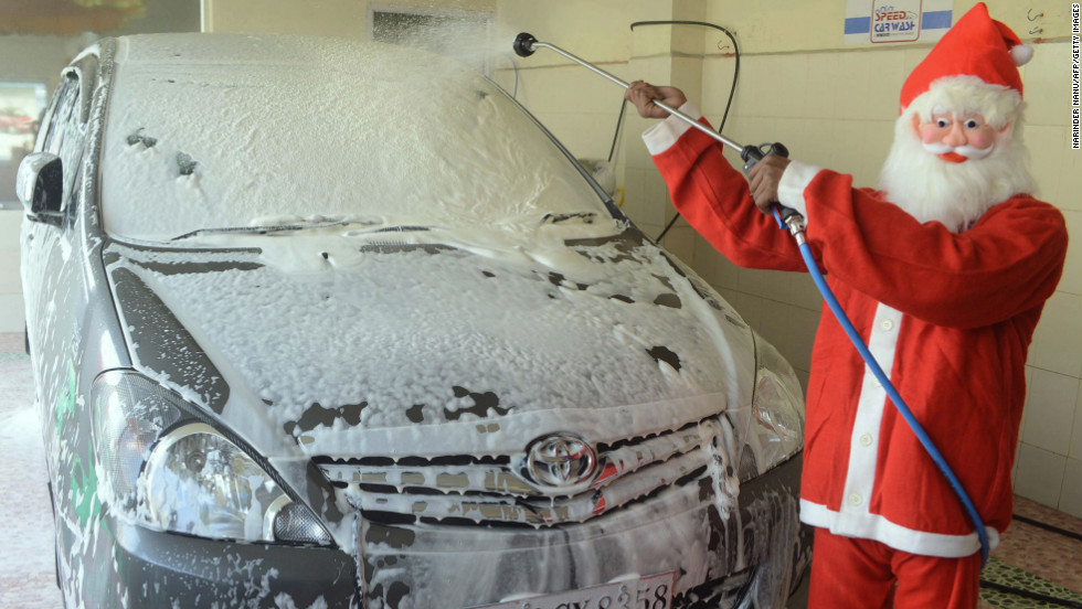 A car wash worker in Santa gear washes a vehicle in Amritsar, India, on December 25.