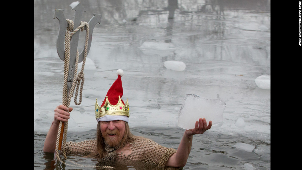 "A member of Berlin's swimming club ""Berliner Seehunde"" (Berlin seals) takes a dip in the Orankesee lake during their traditional Christmas ice swimming session in Berlin, Germany."