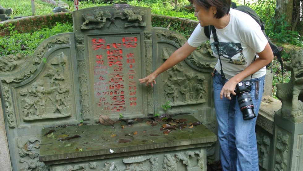 Bukit Brown supporter Claire Leow shows a tour group the grave of Tan Boon Hak.