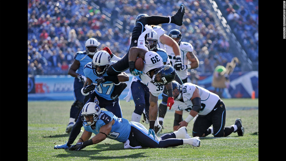 Richard Murphy of the Jacksonville Jaguars is turned head-over-heels by Tommie Campbell and Al Afalava of the Tennessee Titans at LP Field on Sunday in Nashville, Tennessee.
