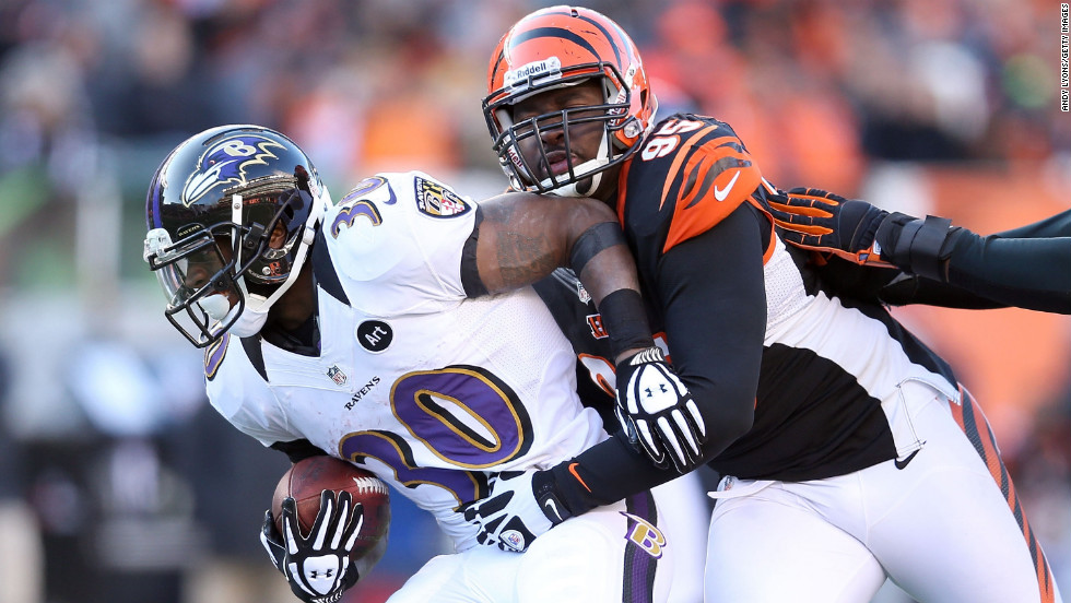 Bernard Pierce of the Baltimore Ravens is tackled by Wallace Gilberry of the Cincinnati Bengals on Sunday.